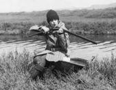 Female hunter with gun near river — Stock Photo