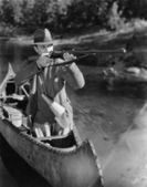 Man aiming gun from canoe — Stock Photo