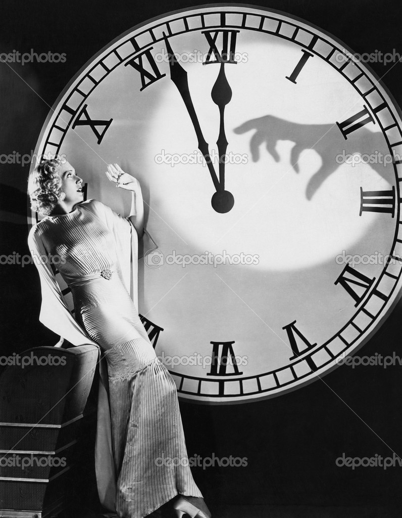 Woman with huge clock recoiling from frightening hand — Stock Photo #12289407