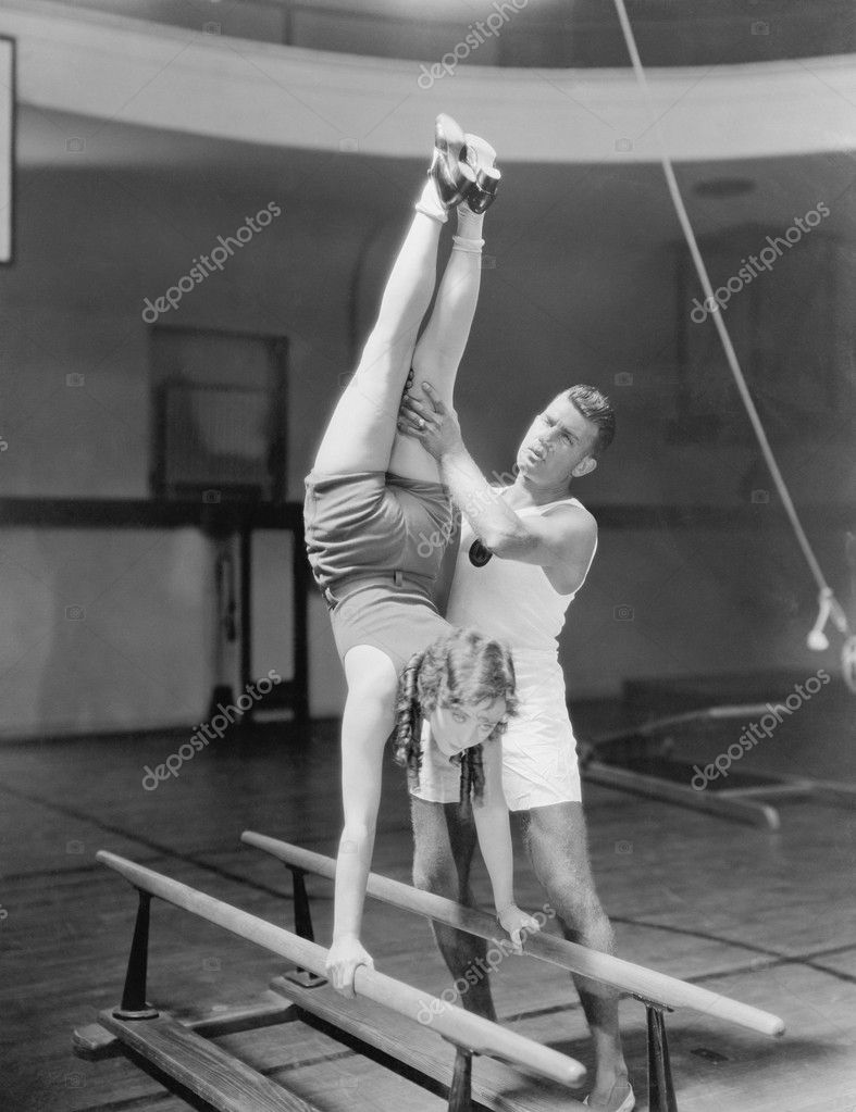Coach helping woman on parallel bars  Stock Photo #12289648