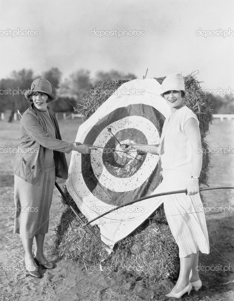 Women with bulls eye in archery target — Zdjęcie stockowe #12289659