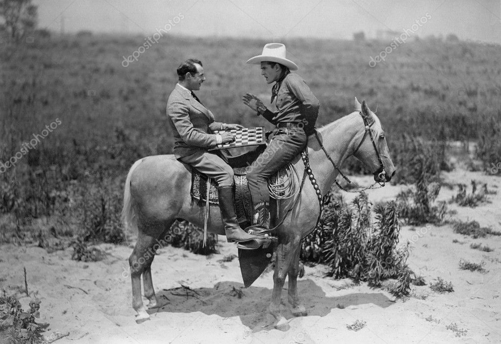 Cowboy and businessman playing checkers on horseback — Stock Photo #12289844