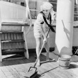 Stock Photo: Female sailor swabbing boat deck