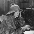 Woman in raincoat sending message in Morse code - Stockfoto