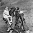 Monkey with golf clubs and toddler girl - Stock Photo