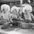 Three women with huge bowls of donuts - Stockfoto