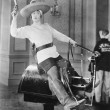 Woman playing cowgirl on mechanical horse - Stockfoto