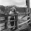 Woman leaning on wooden fence on ranch - Stockfoto