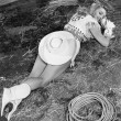 Smiling cowgirl lying on ground - Stockfoto