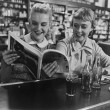 Girlfriends looking at magazine at soda fountain — Foto de Stock