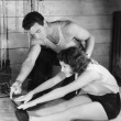 Woman stretching with help from trainer - Stockfoto