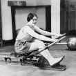 Woman using rowing machine — Stockfoto