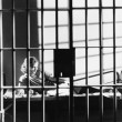 Woman through bars of jail cell - Stock Photo