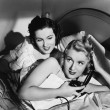 Two women in bed with telephone - Stock Photo
