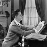 Man at piano writing on sheet music — Stock Photo
