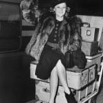 Waving woman sitting on pile of luggage — Stock Photo