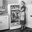 Woman with open refrigerator - Foto de Stock