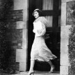 Young woman walking out door — Stock fotografie
