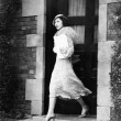 Young woman walking out door — Photo