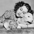 Woman with sleeping lamb and lion cub - Foto Stock