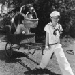 Girl in sailor suit pulling dog in basket — Zdjęcie stockowe