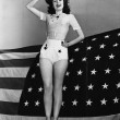 Portrait of woman saluting with American flag - Stock Photo