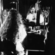 Woman at dressing table looking in mirror - Стоковая фотография