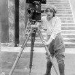 Woman operating movie camera - Stock Photo