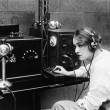 Stock Photo: Womsending Morse code using telegraph