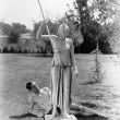 Nude man outside with statue of woman with spear — Stock Photo #12293120