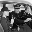 Stockfoto: Womusing radio in car with policeman