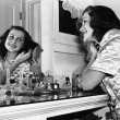 Stock Photo: Young woman brushing hair at dressing table