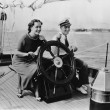 Couple sitting on the deck of a sailboat steering the boat — Stockfoto