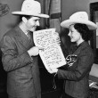 Stock Photo: Couple with cowboy hats looking at sheet music
