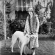 Young woman in coat and hat standing outside with her Russian Wolfhound — Stock Photo