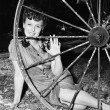 Young womsmiling while sitting behind wagon wheel — Stock Photo #12294082