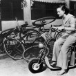 Leaving bicycles in the dust, a young woman fancies a miniature motorbike - Stockfoto