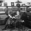 Man sitting in his library reading a book — ストック写真
