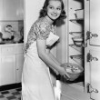 Young woman in an apron in her kitchen taking food out of the refrigerator — Stock Photo #12294204