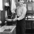 Man in a kitchen pumping water - Stockfoto