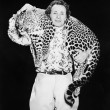 Man posing with a leopard around his neck — 图库照片