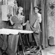 Stock Photo: Man and woman standing in a kitchen while she is ironing his pants and he is behind a curtain