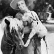 Young woman in a cowboy hat holding a goat while leaning against her pony — Stock Photo