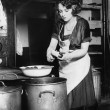 Woman in a kitchen peeling potatoes — ストック写真