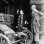 homem e mulher olhando um carro destruído no celeiro — Foto Stock