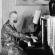Man in a robe playing his piano in the living room — Stockfoto