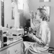 Woman sitting in front of her vanity putting perfume on her eyebrows - Стоковая фотография