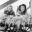 Two women lying in a wagon of hay with their legs in the air — Stock Photo