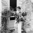 Woman in front of her house gathering flowers in her arms — ストック写真