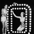 Two young women posing with the letter O — Stockfoto